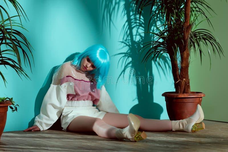 elegancka dziewczyna udaje być obsiadaniem na podłodze między doniczkowym i lalą w błękitnej peruce zdjęcia royalty free