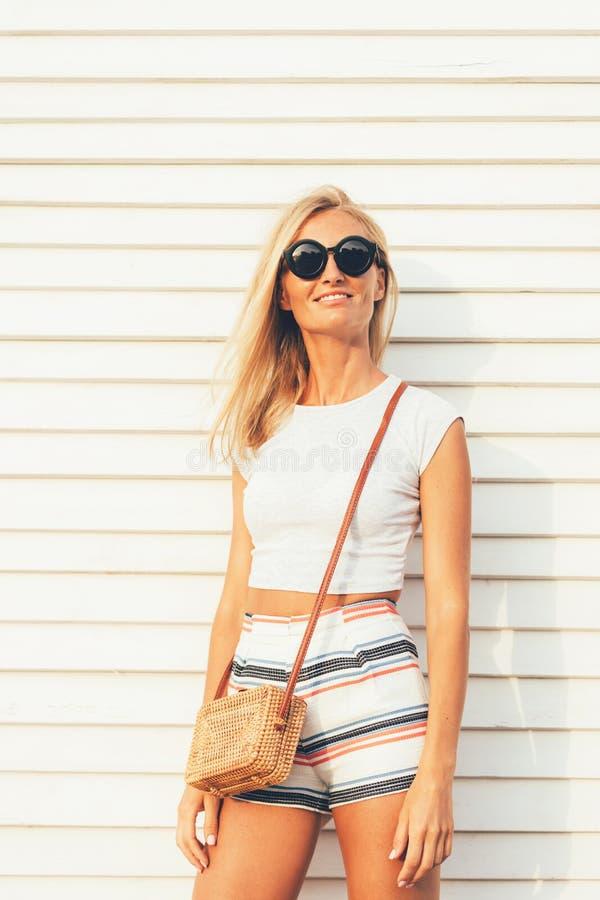 Elegancka dziewczyna w okularach przeciwsłonecznych z modną słomianą torbą i w skrótach i wierzchołku, obraz stock