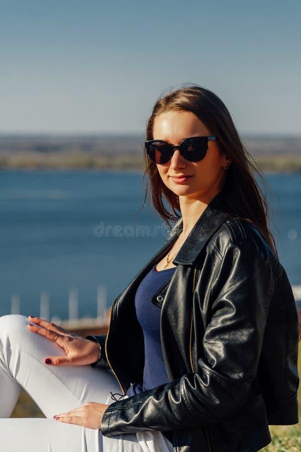 Elegancka dziewczyna w okularach przeciws?onecznych z d?ugie w?osy i sk?rzan? kurtk? zdjęcie royalty free