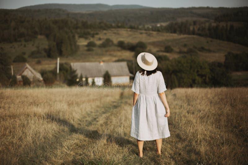 Elegancka dziewczyna w pościeli smokingowy i kapeluszowy chodzący bosym w trawie w pogodnym polu przy wioską Boho kobieta relaksu zdjęcia stock