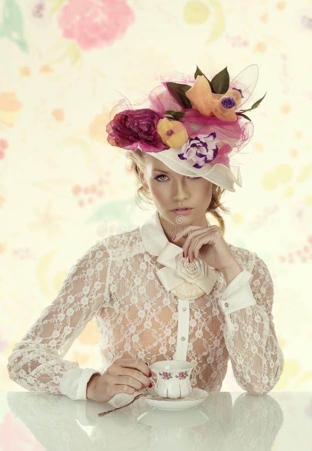 Elegancka dziewczyna z filiżanką herbat spojrzenia wewnątrz obiektyw obrazy royalty free