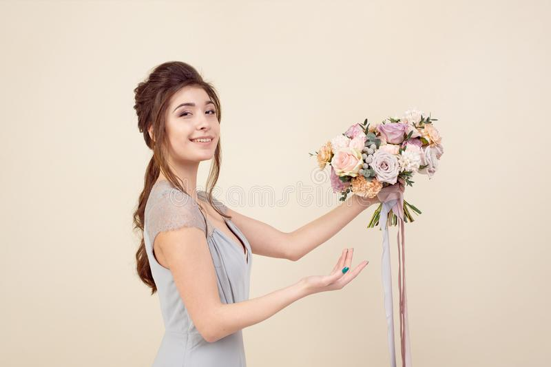 Elegancka dziewczyna z ostrzy?eniem w mi?kkim b??kita makija?u i sukni trzyma bukiet elegancki bukiet kwiaty fotografia royalty free