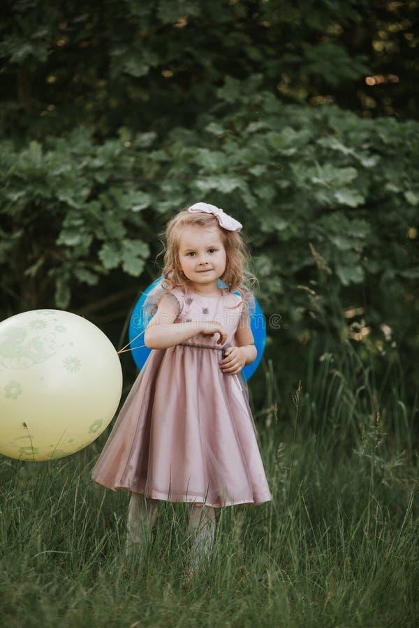 Elegancka dziewczynka trzyma dużego balon jest ubranym modne menchie ubiera w łące figlarnie amerykanin afryka?skiego pochodzenia zdjęcie stock