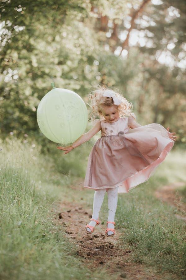 Elegancka dziewczynka trzyma du?ego balon jest ubranym modne menchie ubiera w ??ce figlarnie amerykanin afryka?skiego pochodzenia fotografia stock