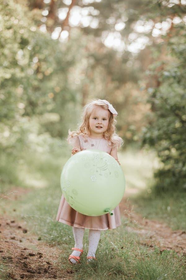 Elegancka dziewczynka trzyma du?ego balon jest ubranym modne menchie ubiera w ??ce figlarnie amerykanin afryka?skiego pochodzenia zdjęcia stock