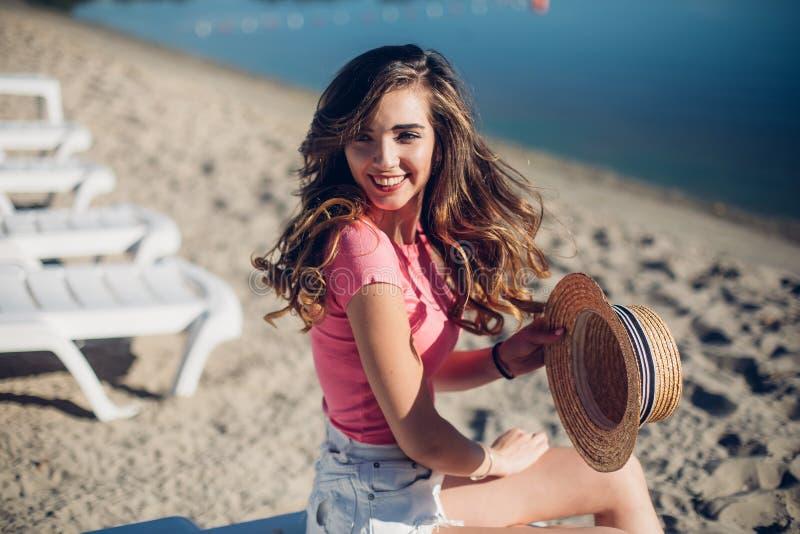 Elegancka emocjonalna dziewczyna jest ubranym, zwiera i słomianego kapelusz i modnego lata kolorowego swimsuit pozować obok egzot fotografia royalty free