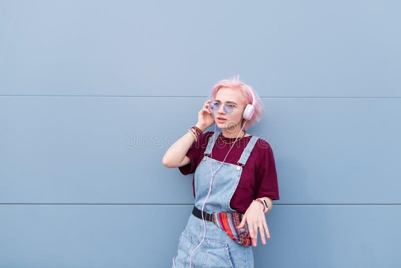 Elegancka hipist dziewczyna z różowymi włosów stojakami na tle błękitna ściana i słucha muzyka w hełmofonach zdjęcie royalty free
