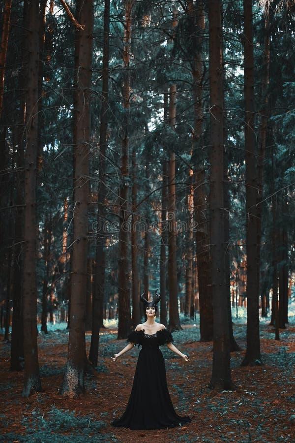 Elegancka i modna brunetka modela dziewczyna w wizerunku Maleficent pozować wśród tajemniczego lasu - bajki opowieść zdjęcie stock