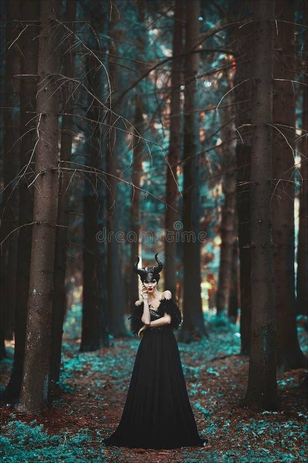Elegancka i modna brunetka modela dziewczyna w wizerunku Maleficent pozowa? w?r?d tajemniczego lasu - bajki opowie?? zdjęcie stock