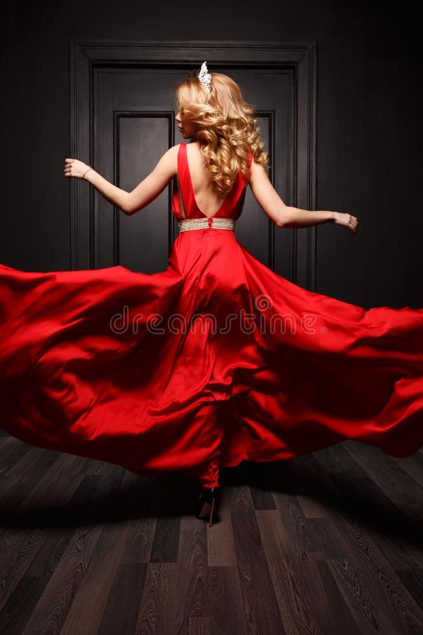 Elegancka i namiętna kobieta z tiarą na jej głowie w czerwonego wieczór trzepotliwej sukni jest zdobyczem w ruchu, wiruje zdjęcia royalty free