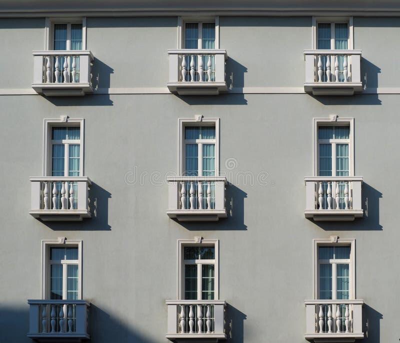 Elegancka jasnopopielata fasada z wielkimi okno i mali biali balkony z kolumnami, w klasycznym stylu obraz stock