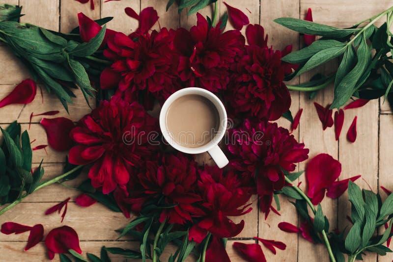 Elegancka kawa i piękne czerwone peonie na nieociosanym drewnianym backgr zdjęcie royalty free