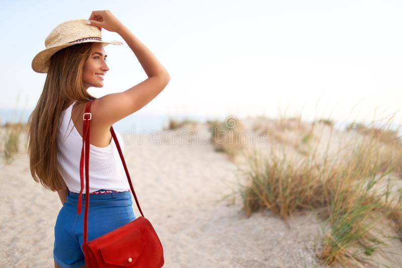 Elegancka kobieta chodzi plaża w słomianym kapeluszu, lato drelichu skrótach i czerwonej modnej torbie, Atrakcyjna garbnikująca k zdjęcie royalty free