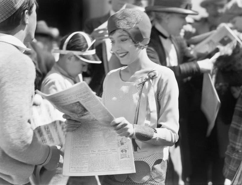 Elegancka kobieta czyta gazetę (Wszystkie persons przedstawiający no są długiego utrzymania i żadny nieruchomość istnieje Dostawc obrazy stock