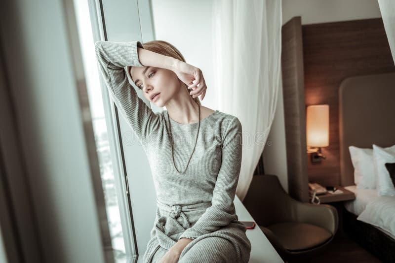 Elegancka kobieta jest ubranym popielatą suknię i akcesoria ma odpoczynek zdjęcie stock