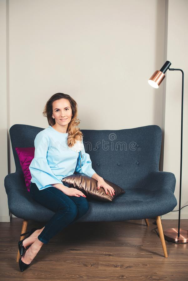 elegancka kobieta Pomyślny biznesowej kobiety obsiadanie na eleganckiej kanapie Uśmiechnięty młody żeński przedsiębiorca przy now zdjęcie royalty free