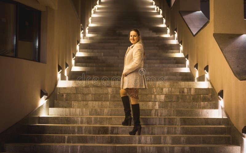 Elegancka kobieta pozuje na iluminującym schody przy nocą zdjęcia royalty free
