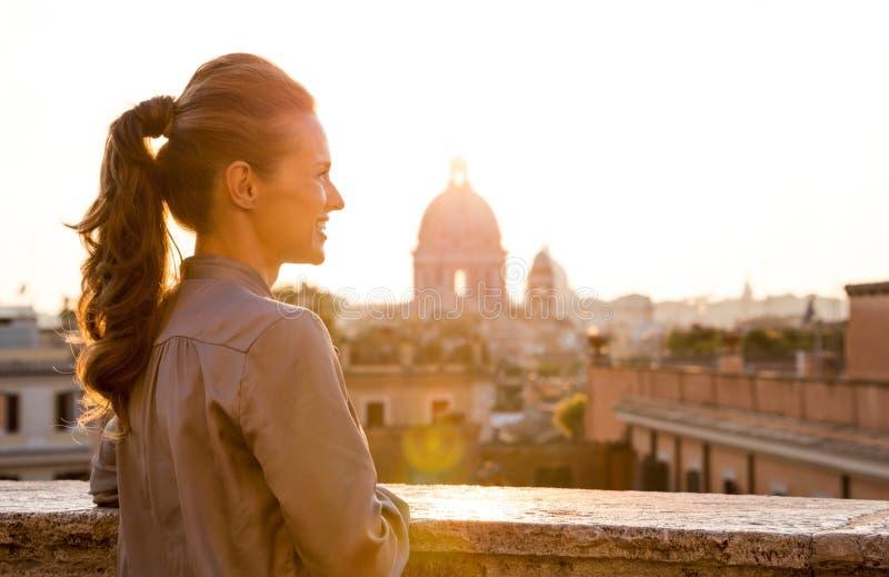 Elegancka kobieta przyglądająca przy zmierzchem nad miastem Rzym out zdjęcie stock