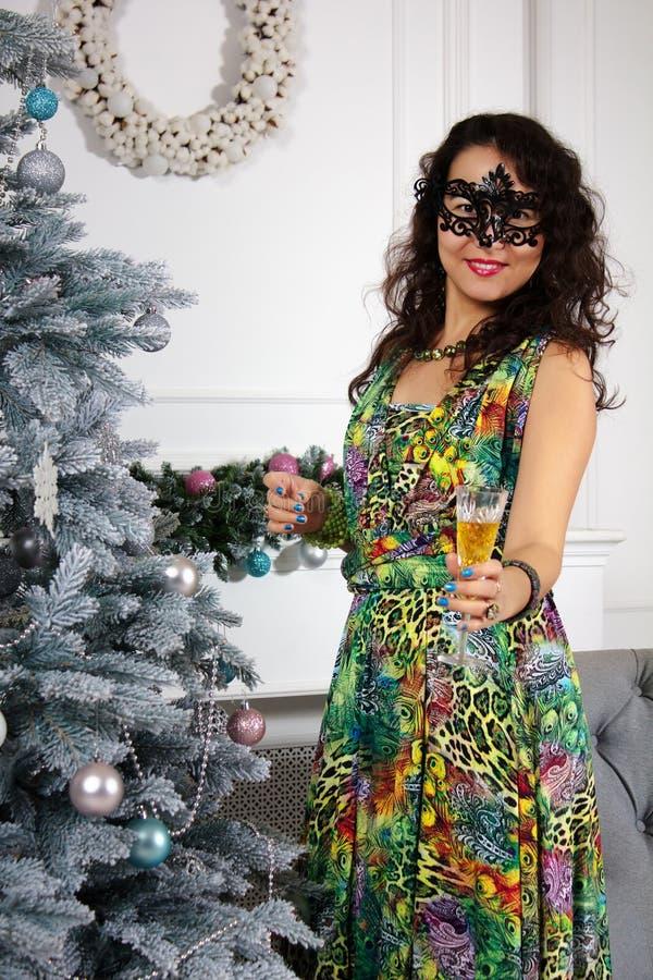 Elegancka kobieta stoi blisko choinki i trzyma szampański w jej ręce w czarnej karnawał masce weared kolorową długą suknię zdjęcie stock