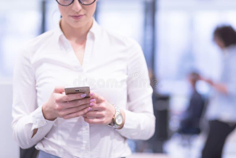 Elegancka kobieta Używa telefon komórkowego w początkowym budynku biurowym obraz royalty free