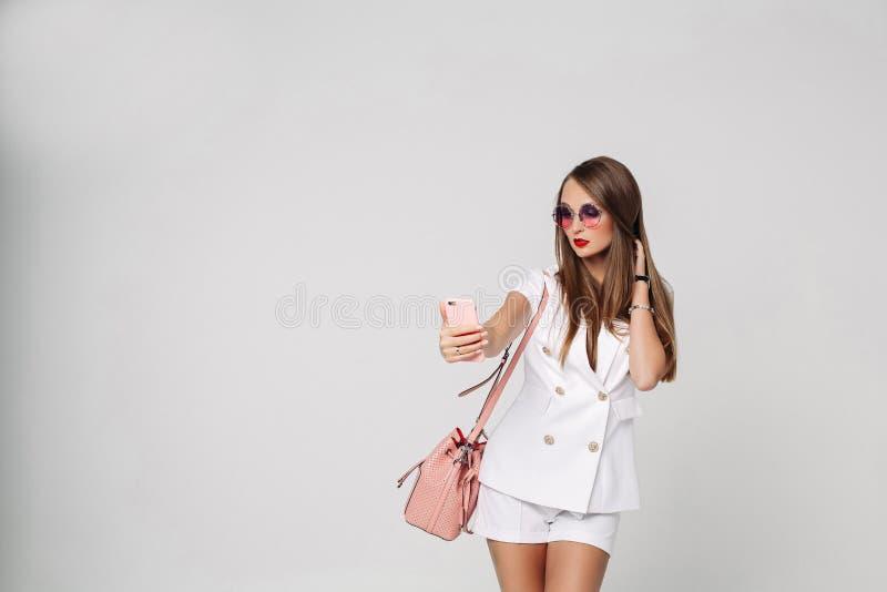 Elegancka kobieta w białym kostiumu i okularach przeciwsłonecznych bierze selfie z wiszącą ozdobą obraz stock