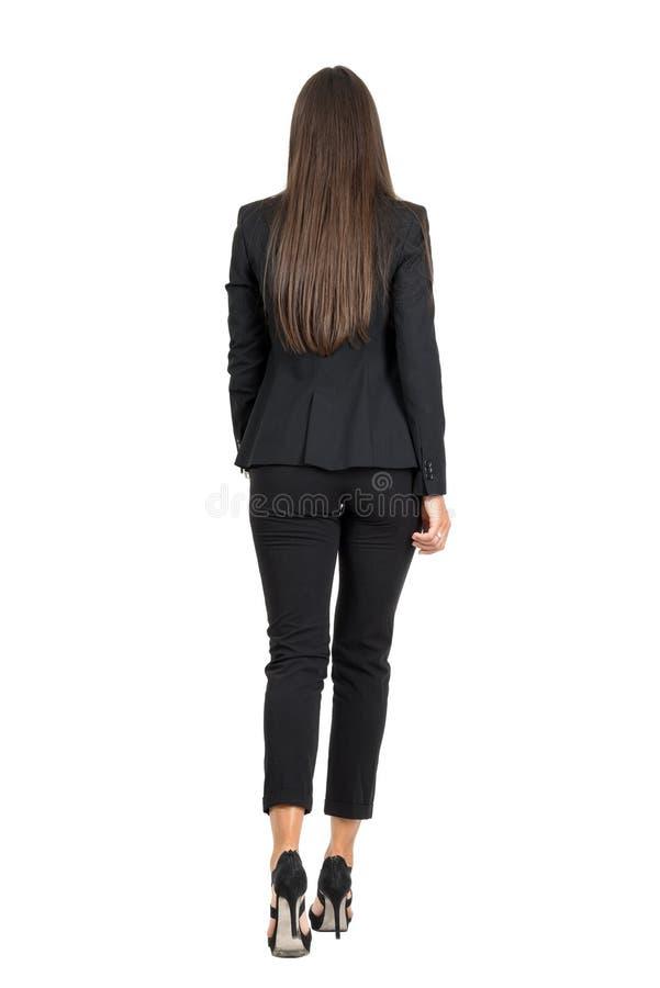 Elegancka kobieta w biznesowym czarnym kostiumu chodzącym daleko od odosobniony tylni widok biel obraz royalty free
