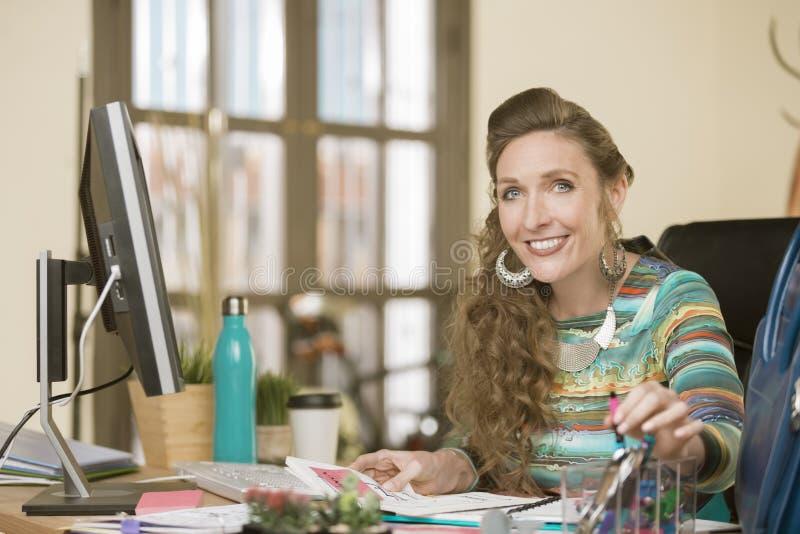 Elegancka kobieta w Cluttered Kreatywnie biurze obraz stock