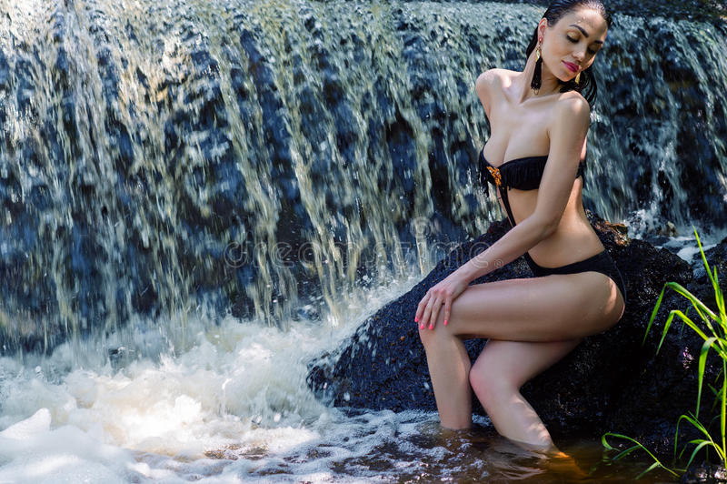 Elegancka kobieta w czarnym swimsuit na tło siklawie zdjęcie royalty free