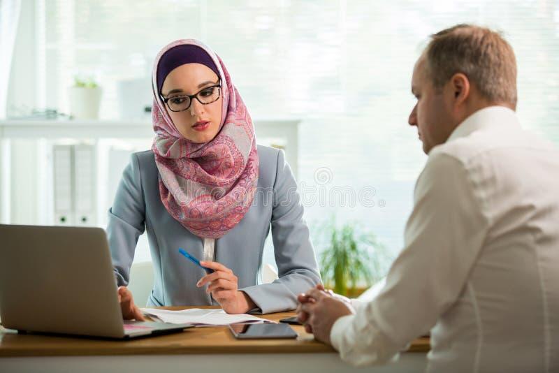 Elegancka kobieta w hijab robi rozmowie przy biurkiem z m??czyzn? fotografia royalty free