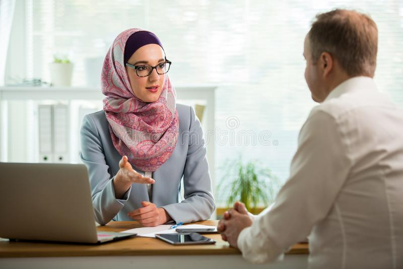 Elegancka kobieta w hijab robi rozmowie przy biurkiem z m??czyzn? zdjęcia royalty free