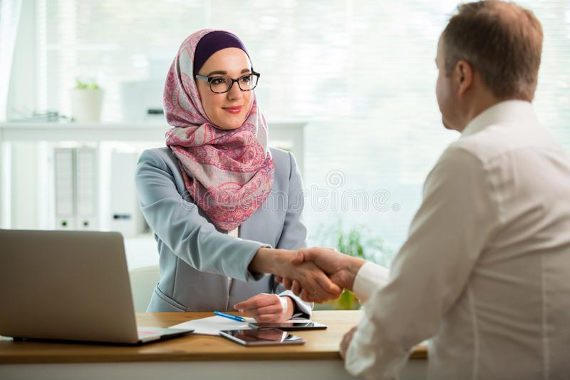 Elegancka kobieta w hijab robi rozmowie przy biurkiem z m??czyzn? zdjęcie stock