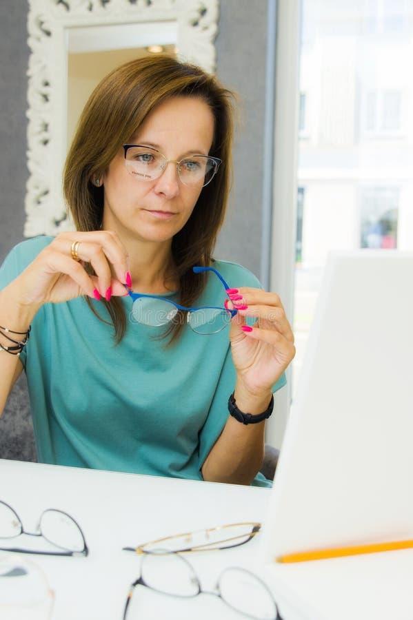 Elegancka kobieta wybiera nowych eyeglasses w okulisty sklepie zdjęcie stock