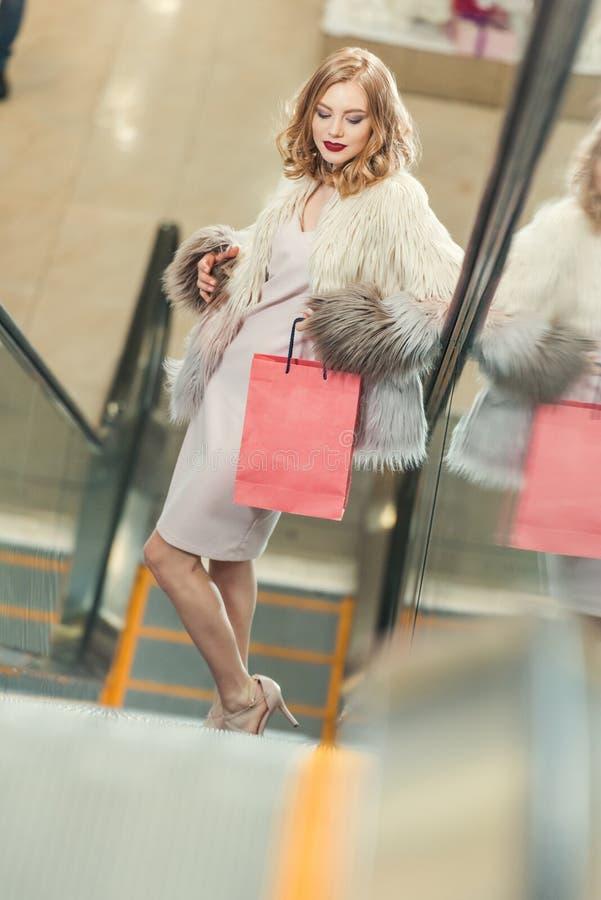 elegancka kobieta z torba na zakupy jeździeckim eskalatorem fotografia royalty free