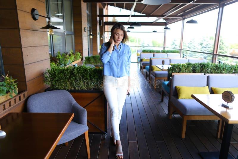 Elegancka kobiety pozycja przy kawiarnią z smartphone i być ubranym spodnia cajgu bielu i koszula zdjęcie stock