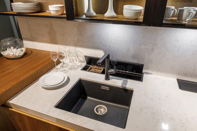 Elegancka kuchnia z tableware i zlew na eleganckim drewnianym kontuarze obrazy stock