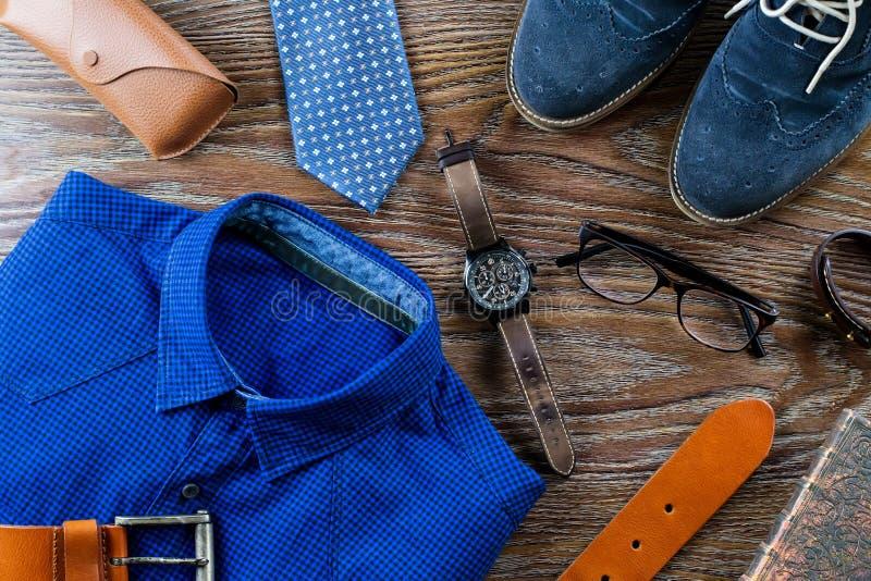 Elegancka mężczyzna odzież i akcesoria mieszkanie kłaść w błękicie i brąz barwi na drewnianym tle obraz stock