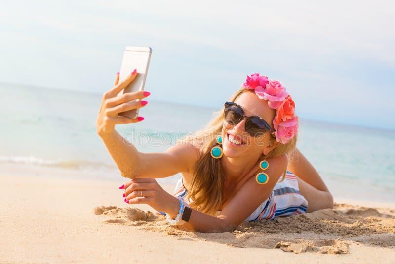 Elegancka młoda ładna kobieta bierze selfie na plaży fotografia stock