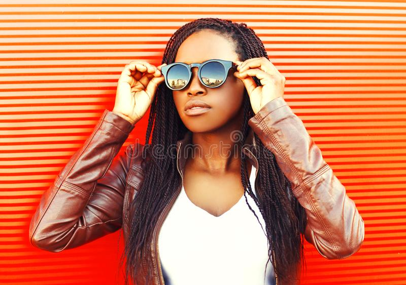Elegancka młoda afrykańska kobieta jest ubranym kurtkę, okulary przeciwsłoneczni w mieście obrazy stock