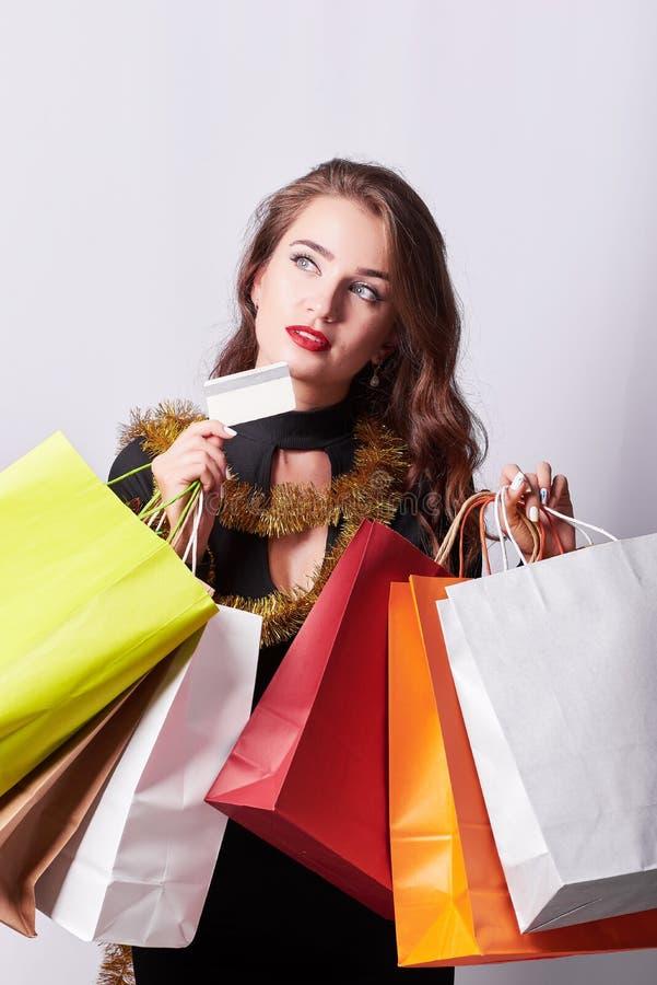 Elegancka młoda brunetki kobieta trzyma kolorowe torby na zakupy i kartę kredytową obraz stock