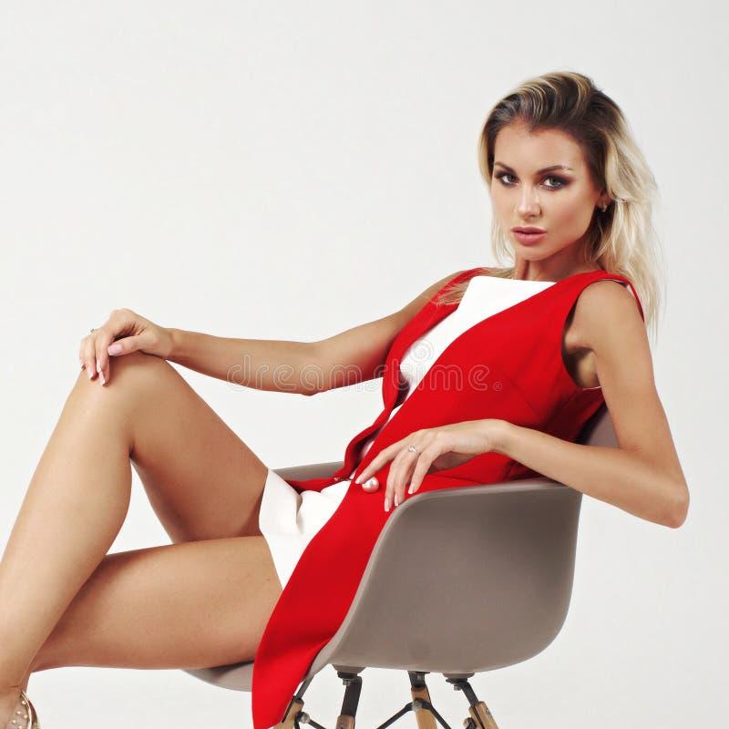 Elegancka młoda kobieta w biel smokingowej i czerwonej kurtce obraz stock