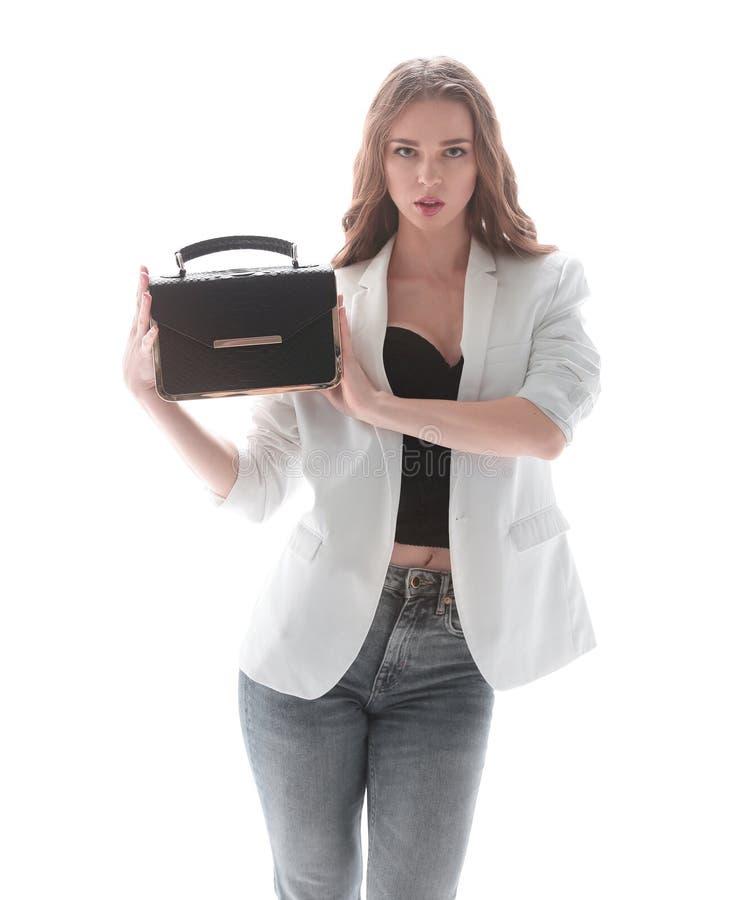 Elegancka m?oda kobieta pokazuje jej modn? torebk? Odizolowywaj?cy na bielu zdjęcie royalty free
