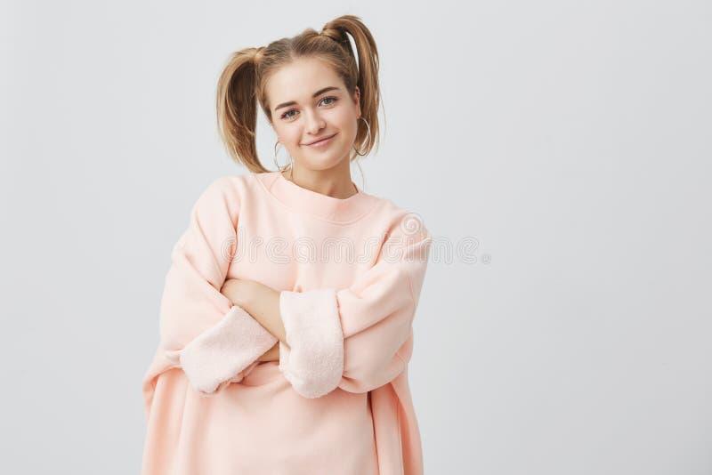 Elegancka, modna, ładna dziewczyna w menchiach, sleeved bluzę sportowa z dwa ponytails i dużym round benclem pozuje przeciw szaro obrazy stock