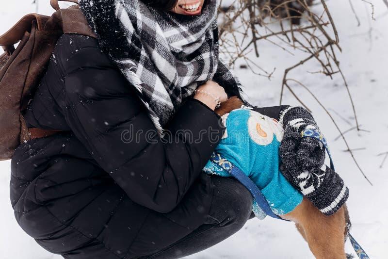 Elegancka modniś kobieta bawić się z ślicznym szczeniakiem w śnieżnym zimnym wint fotografia stock