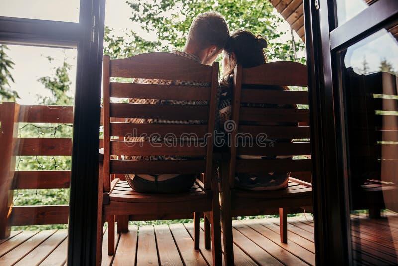 Elegancka modniś para relaksuje na ganeczku, siedzi w drewnianym cott zdjęcia stock