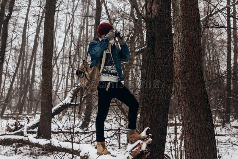 Elegancka modnisia podróżnika mienia kamera i robić fotografia w śniegu zdjęcie stock