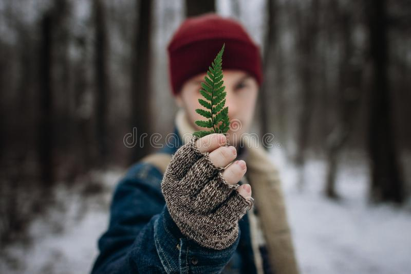 Elegancka modnisia podróżnika mienia zieleni liścia paproć przed fac fotografia stock