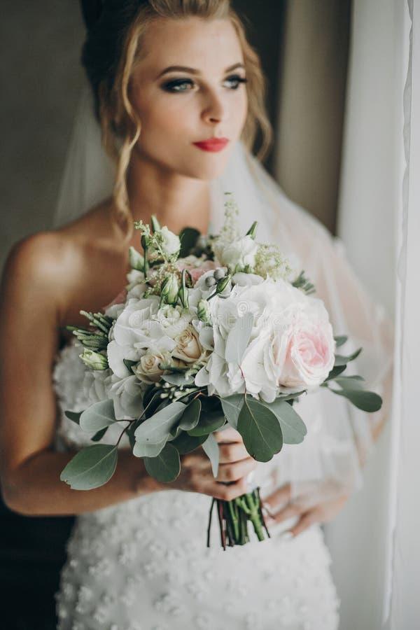 Elegancka panna młoda trzyma nowożytnego ślubnego bukiet i pozuje w miękkim świetle blisko okno w pokoju hotelowym Wspaniały zmys zdjęcia stock