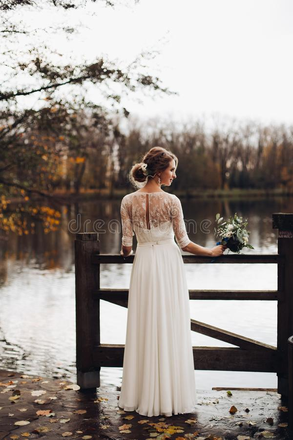 Elegancka panna m?oda w bia?ej ?lubnej sukni z bukietem jeziorem obrazy royalty free