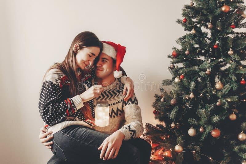 Elegancka para ściska i ono uśmiecha się w pulowerach, trzyma lampion fotografia stock