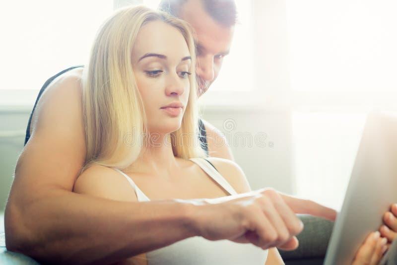 Elegancka para cuddling na kanapie używać cyfrową pastylkę przy ich nowożytnym domem Kobiety mienia pastylka, wyszukuje sieć obrazy royalty free